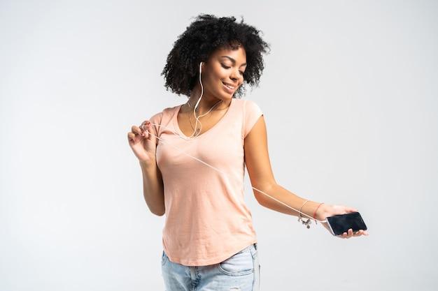 Gelukkig afrikaanse vrouw met afro en casual kleding dansen op de muziek waarnaar ze luistert vanaf haar telefoon.
