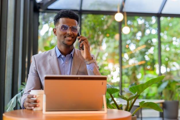 Gelukkig afrikaanse zakenman bij coffeeshop met behulp van laptopcomputer tijdens het praten over de telefoon