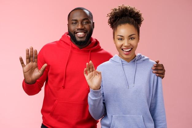 Gelukkig afro-amerikaans koppel man vrouw knuffelen vriendelijke kerel omhelzen meisje ondersteunend samen zwaaien u groeten zeg hallo glimlachend gelukkig uitnodigend komen in gastvrije, staande roze achtergrond