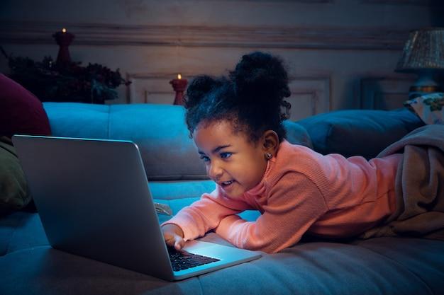 Gelukkig afro-amerikaans meisje tijdens videogesprek met laptop en thuisapparaten, ziet er blij en gelukkig uit. praten met de kerstman voor oudejaarsavond, haar familie, vrienden. interesse en aandacht.
