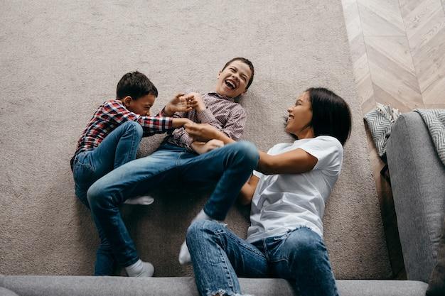 Gelukkig afro-amerikaanse familie moeder en twee zonen gek rond en plezier thuis samen. bovenaanzicht. hoge kwaliteit foto