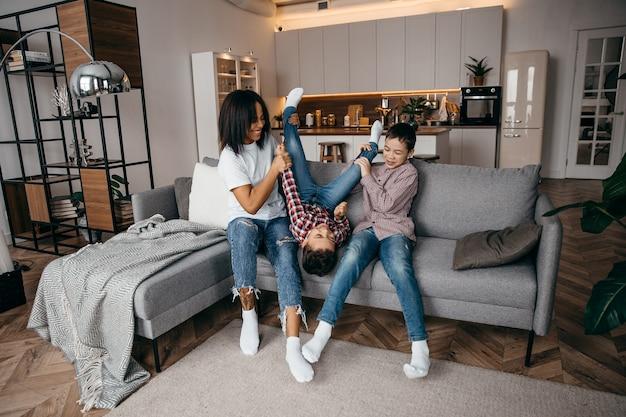 Gelukkig afro-amerikaanse familie moeder en twee zonen gek rond en plezier thuis samen