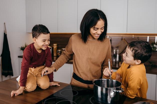 Gelukkig afro-amerikaanse familie moeder en twee zonen plezier koken lunch in de keuken