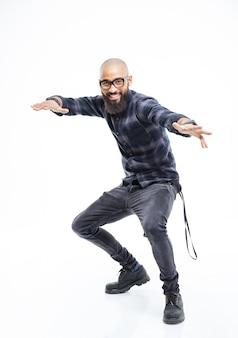 Gelukkig afro-amerikaanse jonge bebaarde man in glazen balanceren en dansen