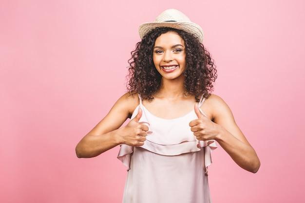 Gelukkig afro-amerikaanse jonge vrouw geïsoleerd op roze achtergrond doet een thumbs-up signaal met haar hand.