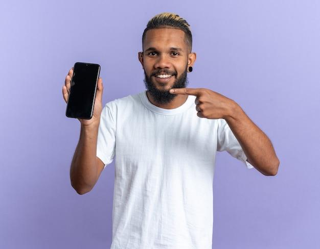 Gelukkig afro-amerikaanse jongeman in wit t-shirt met smartphone wijzend