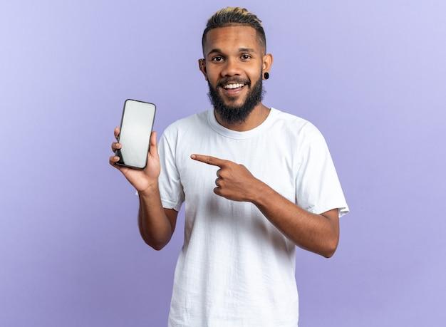 Gelukkig afro-amerikaanse jongeman in wit t-shirt met smartphone wijzend Gratis Foto
