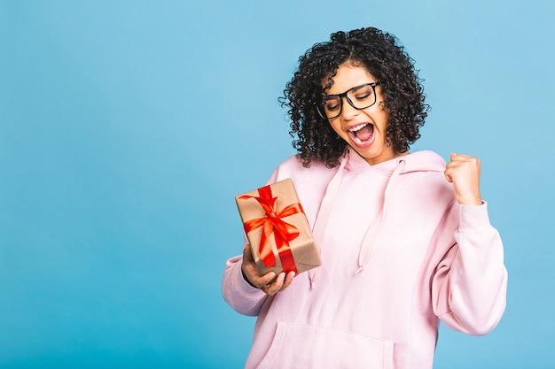 Gelukkig afro-amerikaanse krullende dame in casual lachen terwijl huidige geschenkdoos geïsoleerd op blauwe achtergrond.