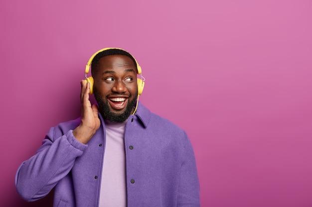 Gelukkig afro-amerikaanse man geniet van liedjes spelen in de koptelefoon, luistert naar aangename melodie, kijkt opzij, heeft een blij humeur, draagt een paarse jas