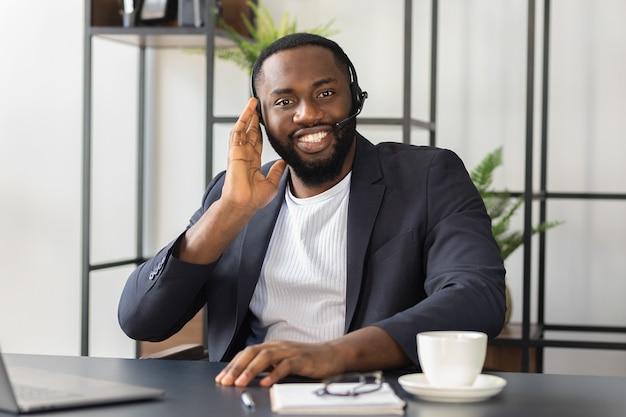 Gelukkig afro-amerikaanse man in headset en pak kijkt naar de camera, glimlachend. succesvolle mannelijke operator van callcenter zit aan de tafel in kantoor. raadpleging van mensen concept