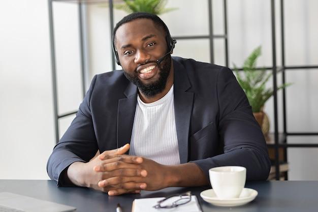 Gelukkig afro-amerikaanse man in headset en pak kijkt naar de camera, glimlachend. succesvolle mannelijke operator van callcenter zit aan de tafel in kantoor.