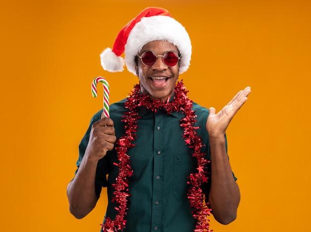 Gelukkig afro-amerikaanse man in kerstmuts met slinger bril houden van snoepgoed glimlachend vrolijk met opgeheven arm staande over oranje muur