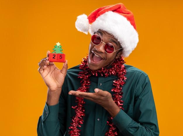 Gelukkig afro-amerikaanse man in kerstmuts met slinger dragen van een zonnebril speelgoed kubussen met datum vijfentwintig presenteren met arm staande over oranje achtergrond