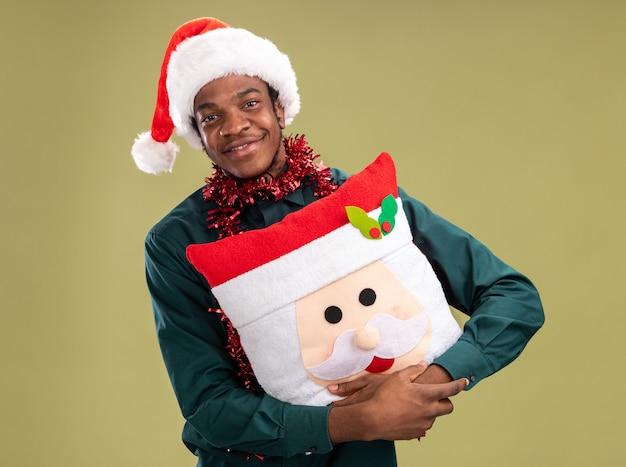 Gelukkig afro-amerikaanse man in kerstmuts met slinger kerst kussen kijken camera met glimlach op gezicht staande over groene achtergrond