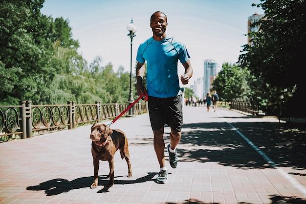 Gelukkig afro-amerikaanse man in sportkleding joggen.