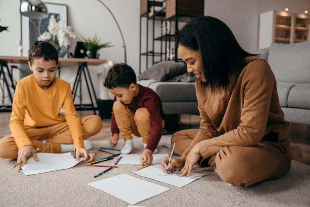 Gelukkig afro-amerikaanse moeder haar zonen leren tekenen met potloden. hoge kwaliteit foto