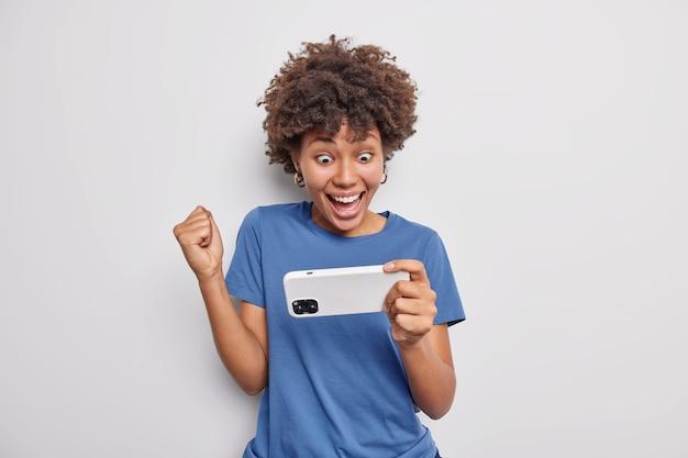 Gelukkig afro-amerikaanse vrouw gekleed in casual blauw t-shirt houdt smartphone horizontaal balt vuist wint online horloges video geïsoleerd over witte muur