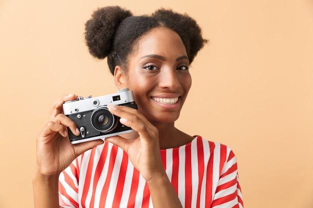 Gelukkig afro-amerikaanse vrouw glimlachend en fotograferen op retro camera, geïsoleerd