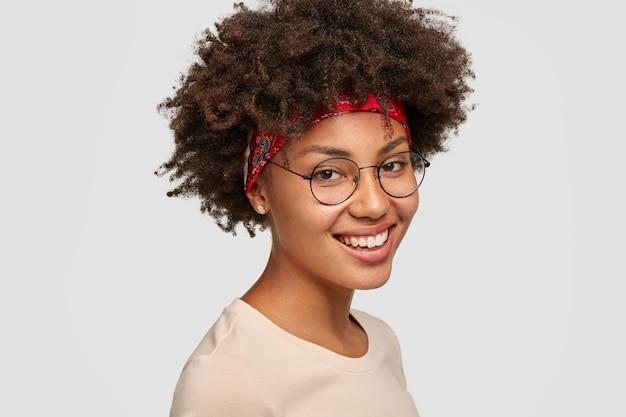 Gelukkig afro-amerikaanse vrouw heeft charmante glimlach, afro-kapsel