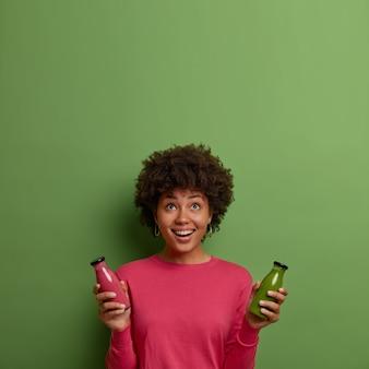Gelukkig afro-amerikaanse vrouw heeft een gezonde maaltijd, houdt aardbei en spinazie smoothie in glazen flessen, drinkt detox drank, houdt zich aan dieet, leidt een gezonde levensstijl, hierboven geconcentreerd op lege ruimte