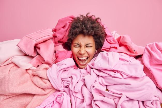 Gelukkig afro-amerikaanse vrouw met krullend haar bedekt met grote hoop kleding verdronken in stapel wasgoed brengt huis in orde roept luid geïsoleerd over roze