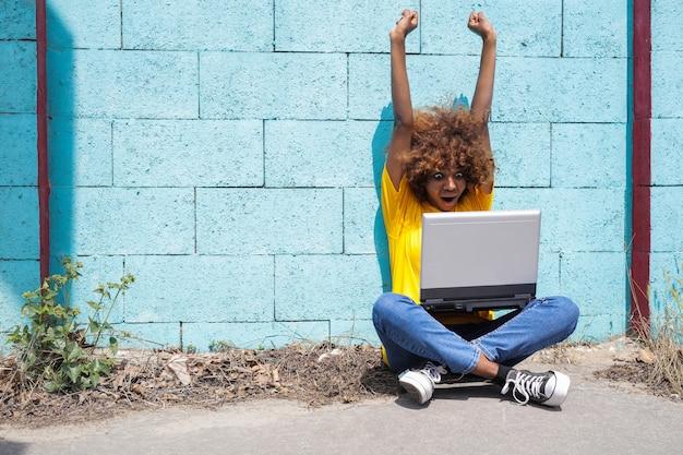 Gelukkig afro-meisje dat goed resultaat online ziet