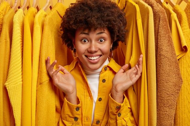Gelukkig afro vrouw met brede glimlach, handpalmen werpt en toont een grote verscheidenheid aan kleding in de winkel, kijkt door gele kleding op hangers