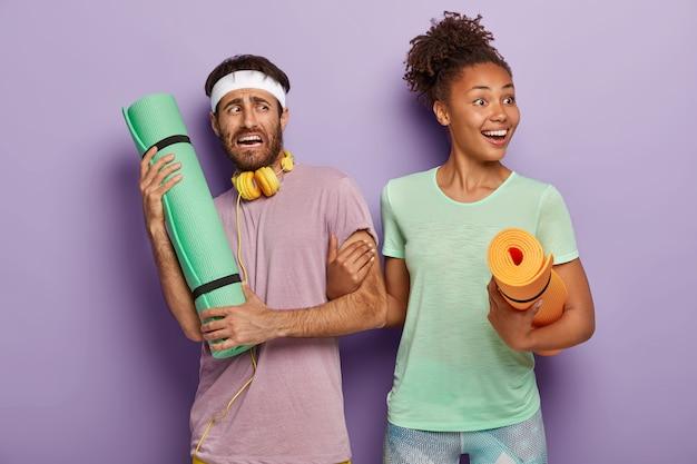 Gelukkig afro-vrouw met fitnessmat, houdt man's hand vast, vraagt om met haar mee te gaan op training, ontevreden man heeft geen verlangen naar sporttraining, draagt hoofdband, t-shirt en koptelefoon. koppel met matten