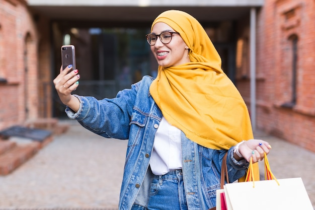 Gelukkig arabisch moslimmeisje met boodschappentassen