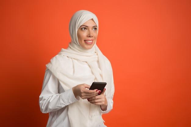 Gelukkig arabische vrouw in hijab met mobiele telefoon.