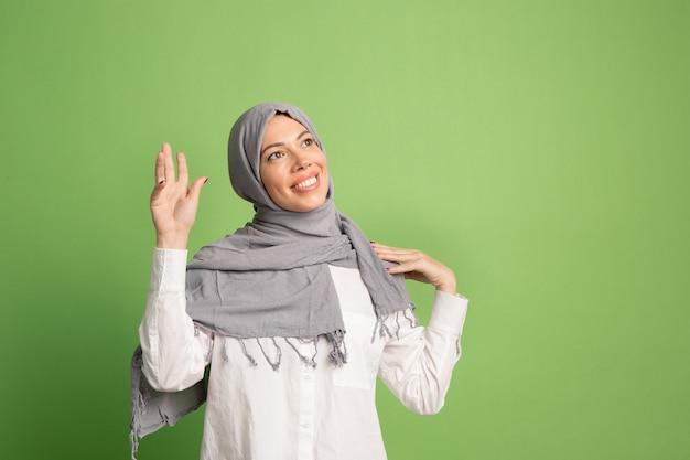 Gelukkig arabische vrouw in hijab. portret dat van glimlachend meisje, bij groene studio stelt.