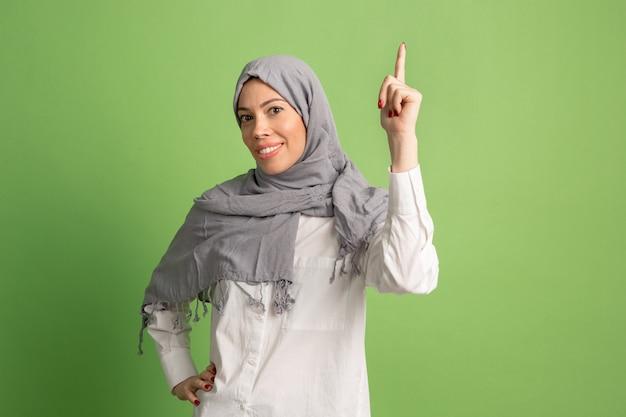 Gelukkig arabische vrouw in hijab. portret dat van glimlachend meisje, bij groene studioachtergrond stelt.