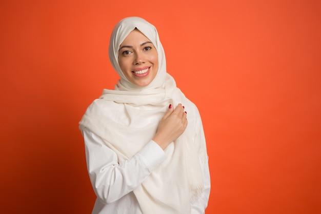 Gelukkig arabische vrouw in hijab. portret dat van glimlachend meisje, bij rode studioachtergrond stelt. jonge emotionele vrouw. de menselijke emoties, gezichtsuitdrukking concept. vooraanzicht.