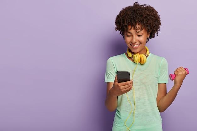 Gelukkig atleet vrouwtje heeft afro kapsel, treinen met halter, luistert naar muziek via koptelefoon, kijkt naar telefoon, gekleed in casual t-shirt