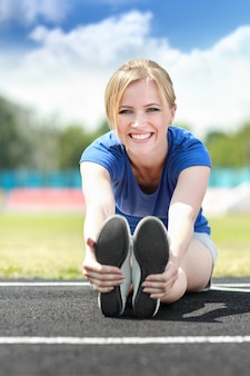 Gelukkig atletisch meisje dat uitrekkende oefening buitenshuis doet