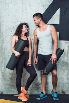 Gelukkig atletisch paar met oefeningsmat die elkaar bekijken