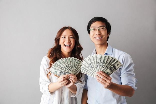 Gelukkig aziatisch bedrijfspaar dat zich geïsoleerd bevindt, die geldbankbiljetten houdt
