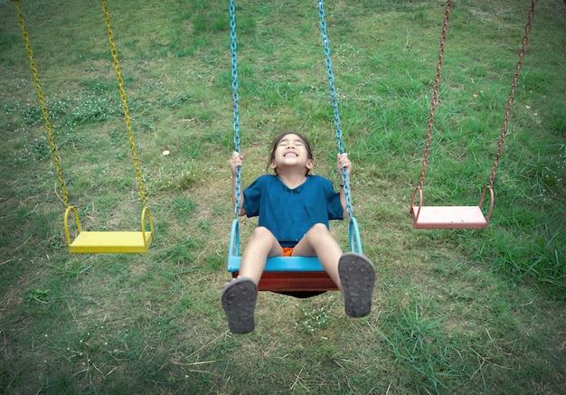 Gelukkig aziatisch de schommelings openluchtplaypark van het jong geitjespel