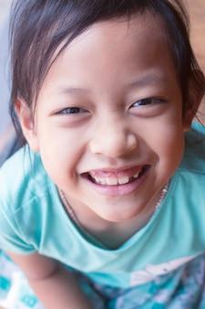 Gelukkig aziatisch en kindmeisje die glimlachen lachen