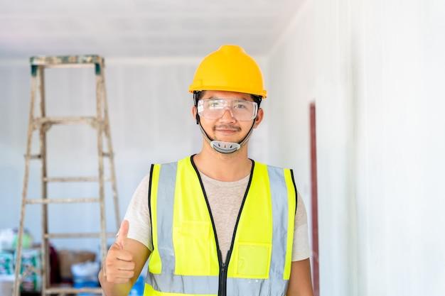 Gelukkig aziatisch ingenieur of architectuur en bouw bedrijfsconcept - zakenman of architect in helm op de bouwplaats, gebouw,