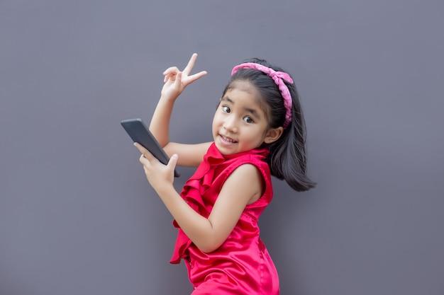 Gelukkig aziatisch jong geitje met mobiele telefoon