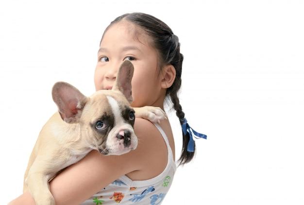 Gelukkig aziatisch jong geitjemeisje die franse buldog houden