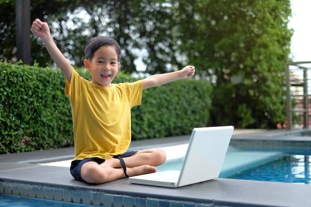 Gelukkig aziatisch jong kind die computerlaptop met hand omhoog aan kant van zwembad met behulp van