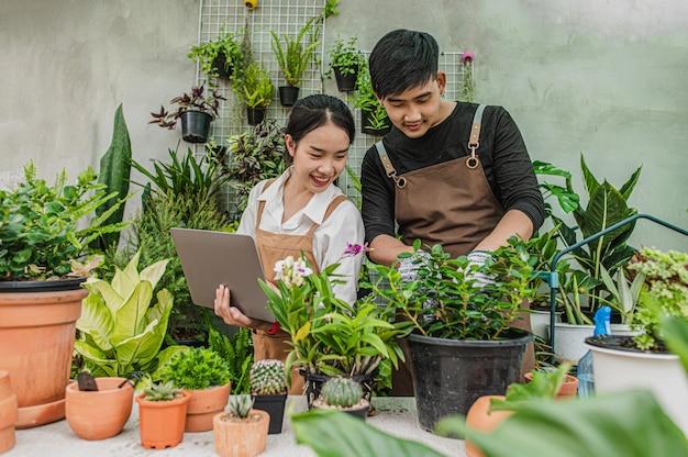 Gelukkig aziatisch jong tuinmannenpaar dat een schort draagt, gebruikt tuinapparatuur en een laptop om voor te zorgen