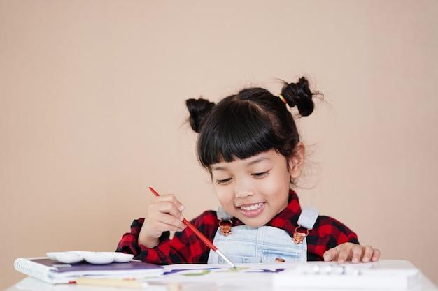 Gelukkig aziatisch kind dat thuis leert en geniet van aquarel tekenen.