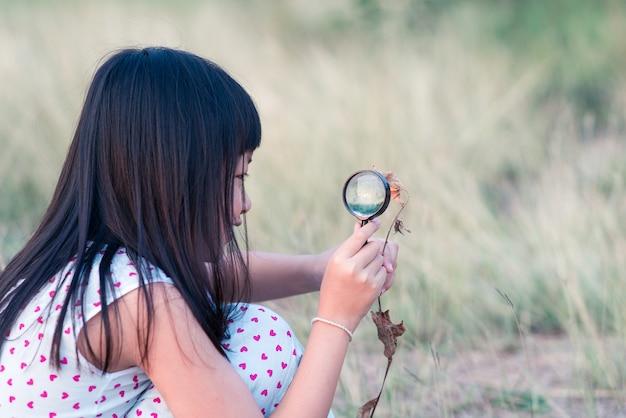 Gelukkig aziatisch kindmeisje dat aard met vergrootglas onderzoekt.
