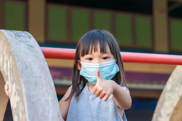 Gelukkig aziatisch kindmeisje dat en stoffenmasker glimlacht draagt. ze speelt met speelgoed met schuifbalk in de speeltuin,