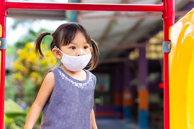 Gelukkig aziatisch kindmeisje dat en stoffenmasker glimlacht draagt, zij speelt met het stuk speelgoed van de schuifbalk bij de speelplaats.