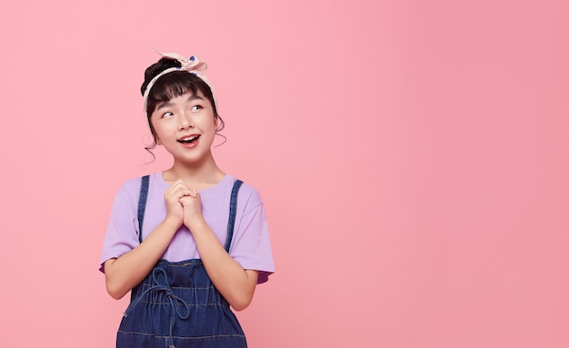 Gelukkig aziatisch kindmeisje dat op roze exemplaarruimtemuur wordt geïsoleerd.
