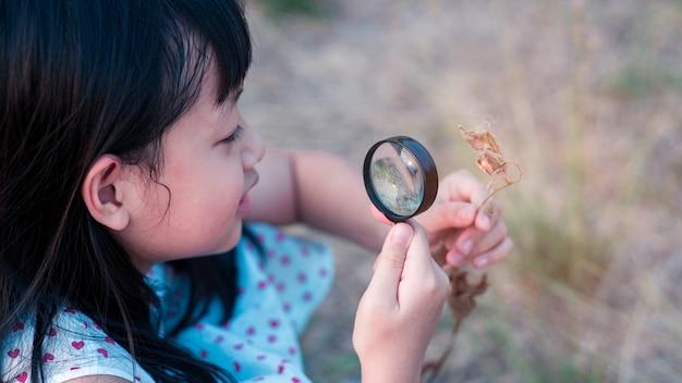 Gelukkig aziatisch kindmeisje die aard met vergrootglas onderzoeken stijl 16: 9
